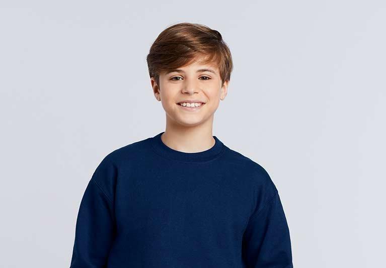 Lächelnder Junge im dunkelblauen Gildan Sweater