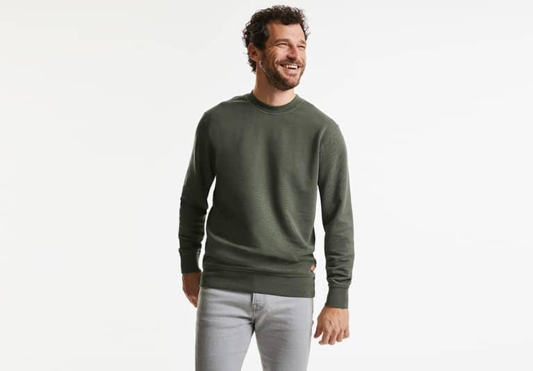 Lachendes männliches Model mit dunkelgrünem Russell Sweatshirt